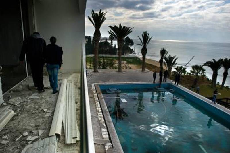 People walk on the balcony overlooking the pool as they visit the burnt and looted house that belonged to the nephew of ousted Tunisian President Zine El Abidine Ben Ali in Hammamet, some 60 kms south-east of Tunis, on January 19, 2011. Hundreds of people protested in the centre of Tunis on January 19, calling for the government to resign and for the abolition of the RCD, the former ruling party under Tunisia's authoritarian regime.    AFP PHOTO / MARTIN BUREAU