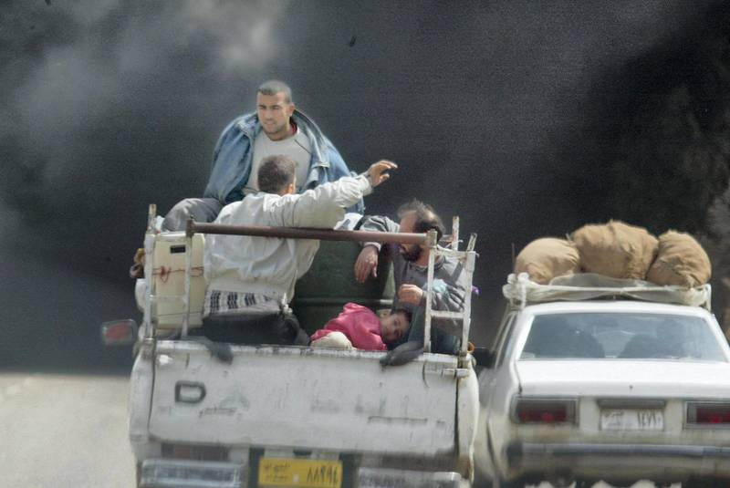 Iraqis fleeing Baghdad sit with their belongings in the back of a pick-up truck 31 March 2003, as smoke billowing from burning oil trenches covers the sky. Coalition warplanes pounded the Iraqi capital and its outskirts, with loud explosions rocking the city.    AFP PHOTO/Ramzi HAIDAR (Photo by RAMZI HAIDAR / AFP)