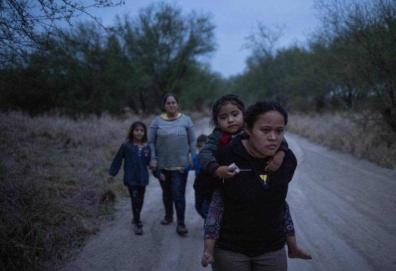 Taznari, an asylum-seeking migrant woman from Honduras, carries her three-year-old daughter, also named Taznari, down a dirt road after they crossed the Rio Grande river into the United States from Mexico on a raft in Penitas, Texas, U.S., March 16, 2021. REUTERS/Adrees Latif