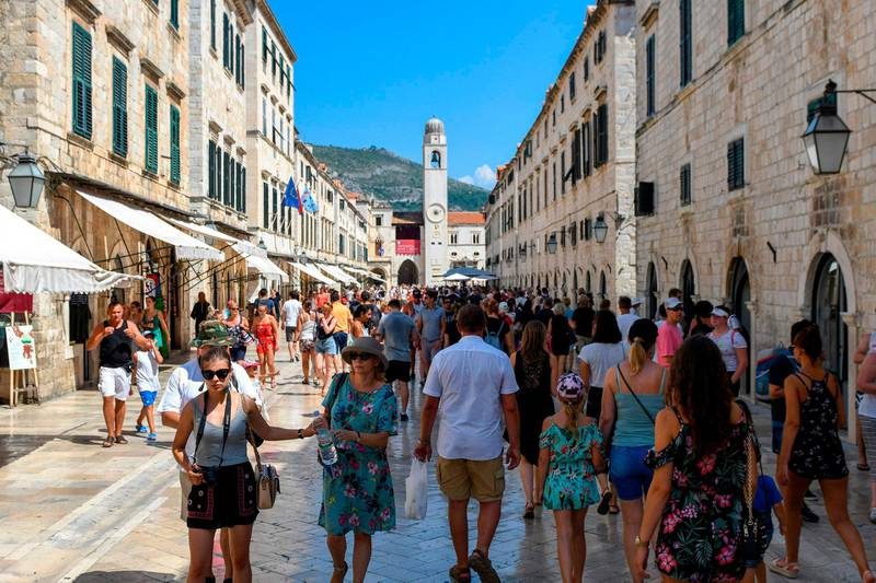 """Tourists stroll in a street as they visit the centre of Dubrovnik on August 6, 2018. - Montenegro's medieval walled city of Kotor, an Adriatic seaport cradled in a spectacular fjord-like bay, has survived centuries of weather and warfare. Now it is facing a different kind of assault, that of gargantuan cruise ships disgorging throngs of tourists threatening a place that was only a few years ago commonly described as a """"hidden gem"""". (Photo by Savo PRELEVIC / AFP)"""