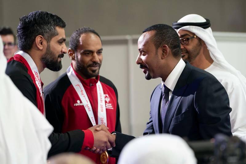 ABU DHABI, UNITED ARAB EMIRATES - March 20, 2019: HE Abiy Ahmed, Prime Minister of Ethiopia (R) greets  an athlete during the Special Olympics World Games Abu Dhabi 2019 at Abu Dhabi National Exhibition Centre. Seen HH Sheikh Mohamed bin Zayed Al Nahyan, Crown Prince of Abu Dhabi and Deputy Supreme Commander of the UAE Armed Forces (Back R).  ( Mohamed Al Hammadi / Ministry of Presidential Affairs ) ---