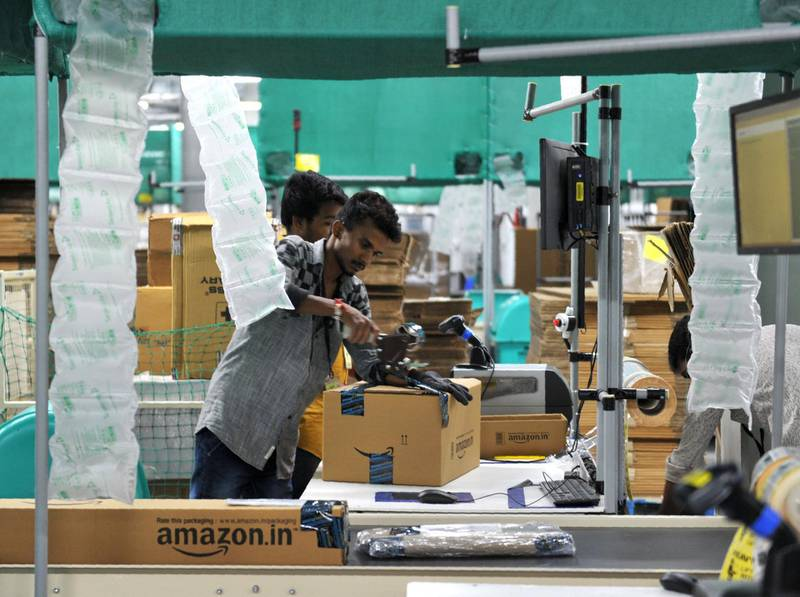 Indian employees work inside Amazon's largest Fulfillment Centre (FC) in India, on the outskirts of Hyderabad on September 7, 2017. / AFP PHOTO / NOAH SEELAM