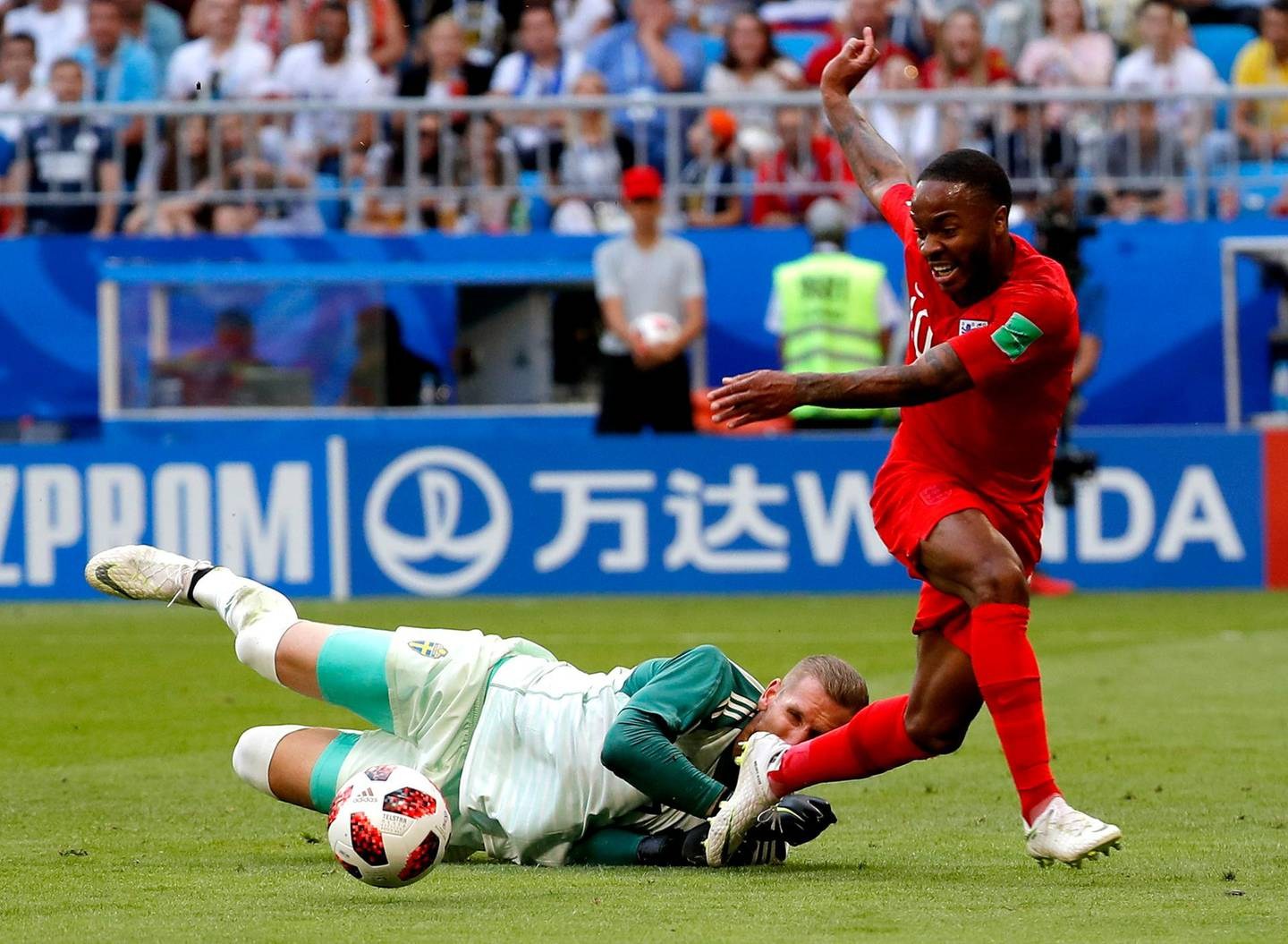 epa06871422 Raheem Sterling of England (R) and goalkeeper Robin Olsen of Sweden in action during the FIFA World Cup 2018 quarter final soccer match between Sweden and England in Samara, Russia, 07 July 2018.  (RESTRICTIONS APPLY: Editorial Use Only, not used in association with any commercial entity - Images must not be used in any form of alert service or push service of any kind including via mobile alert services, downloads to mobile devices or MMS messaging - Images must appear as still images and must not emulate match action video footage - No alteration is made to, and no text or image is superimposed over, any published image which: (a) intentionally obscures or removes a sponsor identification image; or (b) adds or overlays the commercial identification of any third party which is not officially associated with the FIFA World Cup)  EPA/SERGEI ILNITSKY   EDITORIAL USE ONLY