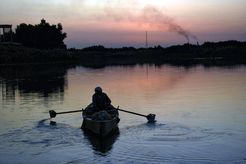 A man sails on the Euphrates river at sunset in the Iraqi city of Nasiriyah in the Dhi Qar province, about 360 kms southeast of the capital Baghdad , on December 30, 2020. (Photo by Asaad NIAZI / AFP)