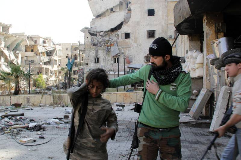 Syrian youth Ahmed, 13-years old (L) and Faris (R), 16-years old, who allegedly fight alongside opposition fighters from the Sadeq Al-Amin Brigade, get prepared with another member of the brigade before a patrol in the Salah al-Din neighbourhood of the northern Syrian city of Aleppo on November 17, 2013. For three weeks, the army has been pressing a campaign to retake rebel-held areas in Aleppo, particularly east of the country's second city, and jihadist fighters have called for mass mobilisation to counter regime advances. AFP PHOTO / KARAM AL-MASRI (Photo by KARAM AL-MASRI / AFP)