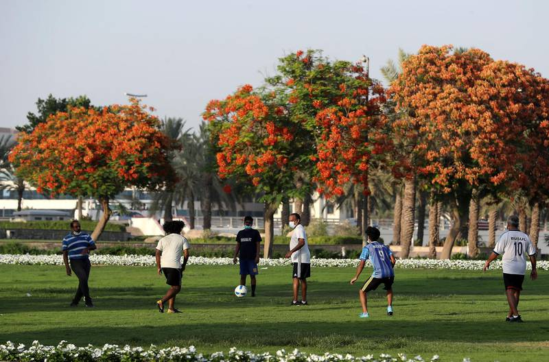 DUBAI, UNITED ARAB EMIRATES , May 27 – 2020 :- People wearing protective face mask as a preventive measure against the spread of coronavirus and playing football in the green area outside the closed Zabeel park in Dubai. (Pawan Singh / The National) For News/Online/Stock/Instagram