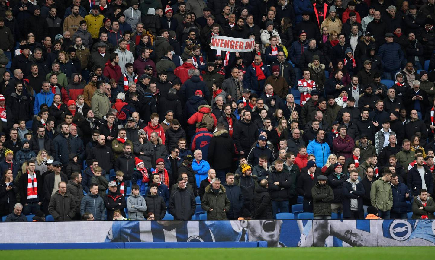 """Soccer Football - Premier League - Brighton & Hove Albion vs Arsenal - The American Express Community Stadium, Brighton, Britain - March 4, 2018   Arsenal fans display banners in reference to manager Arsene Wenger   Action Images via Reuters/Tony O'Brien    EDITORIAL USE ONLY. No use with unauthorized audio, video, data, fixture lists, club/league logos or """"live"""" services. Online in-match use limited to 75 images, no video emulation. No use in betting, games or single club/league/player publications.  Please contact your account representative for further details."""