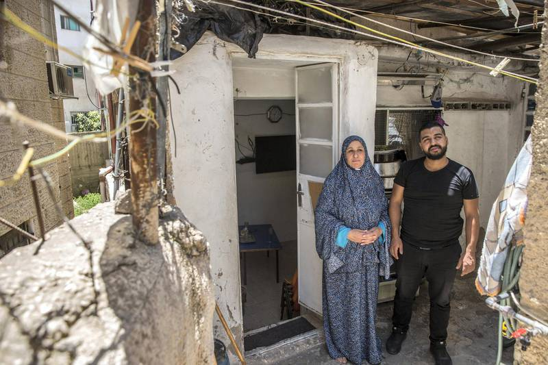 Motes Abu Khader,26, and his mother Nada.47,outside  their hime in the Aida refugee camp near the Palestinian city of Bethlehem on June 23,2019. Eight family members live in the home . Photo by Heidi Levine for The National
