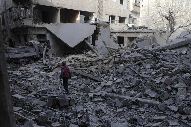 TOPSHOT - A Syrian boy walk past destruction following government air strikes in the Eastern Ghouta rebel-held enclave of Douma, on the eastern outskirts of the capital Damascus on March 19, 2018. At least 20 civilians have died in a resumption of bombing on Douma, the largest town in shrinking rebel-controlled pockets of Syria's Eastern Ghouta, a monitor said. The fresh bloodshed came after a week-long lull in the bombardment of Douma after negotiations between rebels and regime-backer Russia allowed medical evacuations from the town. / AFP PHOTO / HAMZA AL-AJWEH
