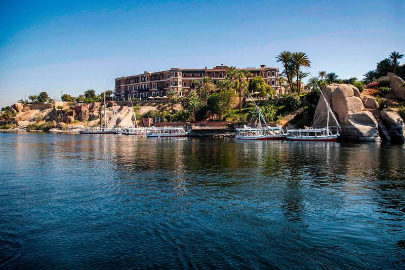 """This picture taken on January 3, 2021 shows a Nile view of the Old Cataract Hotel overlooking the river in Egypt's southern city of Aswan, some 920 kilometres south of the capital, where British crime fiction writer Dame Agatha Christie is believed to have stayed while writing her 1937 novel """"Death on the Nile"""". Over a century since it first cruised the glittering waters of the Nile, the steam ship """"Sudan"""" draws tourists following the trail of legendary crime novelist Agatha Christie, whom it was inspired to pen one of her most famous whodunnits in 1937, """"Death on the Nile"""". / AFP / Khaled DESOUKI"""