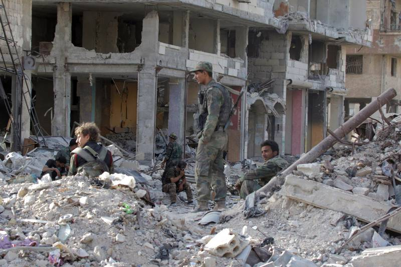 epa06754751 Syrian soldiers sit in the rubble al-Hajar al-Aswad neighborhood in south Damascus, Syria, 21 May 2018. According to reports, the Syrian army claims it has regained full control over Damascus' surrounding areas. State TV reports that the army cleared the area and the adjacent al-Yarmouk camp after killing large number of ISIS fighters.  EPA/YOUSSEF BADAWI