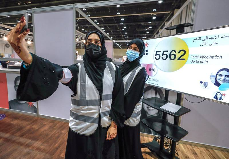 Abu Dhabi, United Arab Emirates, August 6, 2020.  Volunteers take a selfie in front of the monitor at the ADNEC volunteer facility showing that the five thousand total vaccination record has been broken.Victor Besa /The NationalSection: NAReporter:  Shireena Al Nowais