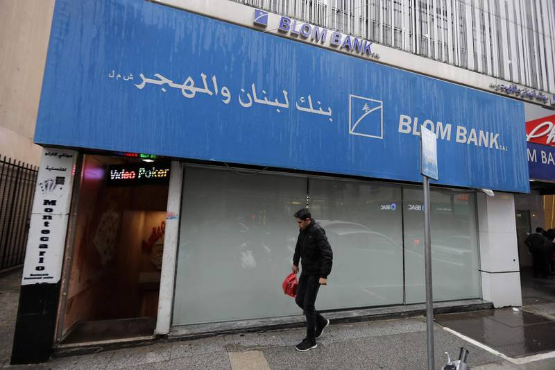 A man walks in front of a bank in the capital Beirut on March 6, 2020. Lebanon's central bank today ordered money changers to cap their exchange rate at no more than 30 percent above the official peg to contain the pound's devaluation on the parallel market. Debt-ridden Lebanon is facing its most serious economic crisis since the end of its 1975-1990 civil war.  / AFP / JOSEPH EID
