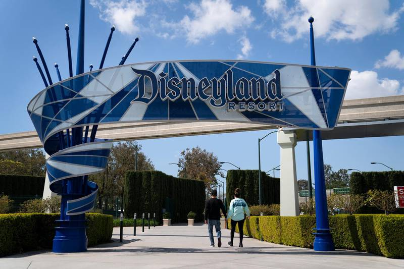 FILE - Two visitors enter Disneyland Resort in Anaheim, Calif., on March 9, 2021. Disneyland said Thursday, April 8, 2021, that its new Avengers Campus will debut on June 4, nearly a year after originally planned. (AP Photo/Jae C. Hong)