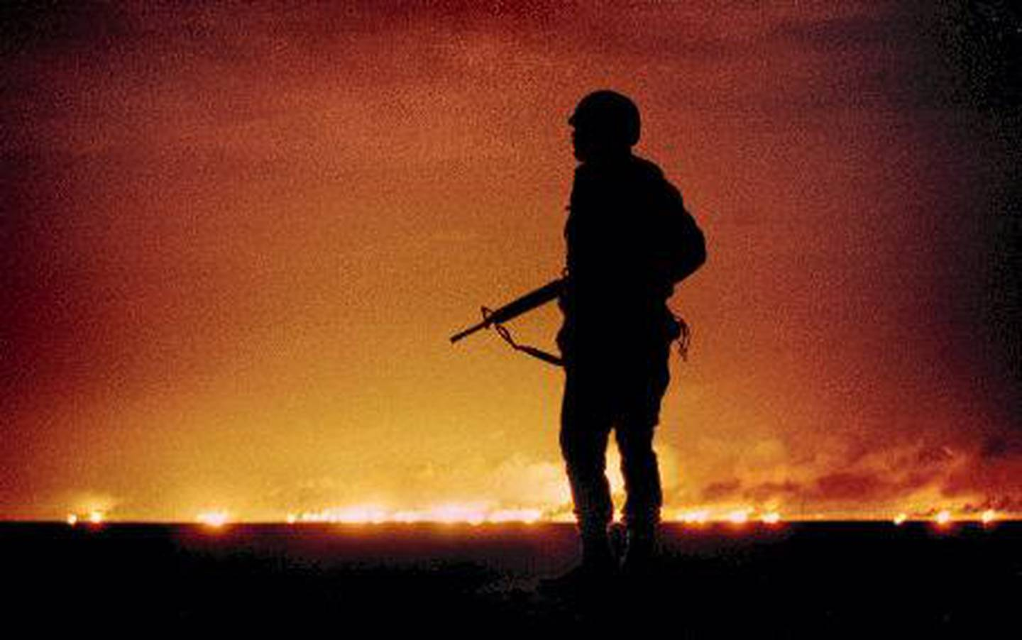 - FILE PHOTO 26FEB91 - A file photo dated February 26, 1991 of a U.S. soldier standing night guard as oil wells burn in the distance in Kuwait, just south of the Iraqi border on the last night of the Gulf War. Hundreds of burning oil wells lit up the sky after they were sabotaged by retreating Iraqi soldiers.  January 17, 2001 is the 10th anniversary of the commencement of the coalition's Desert Storm air and bombing campaign to free Kuwait from Iraqi occupation.