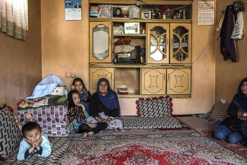 Mr Gul's family sits in their living room, a photo of the children's mother on top of the shelf. She was killed in the attack on a Kabul aternity ward that hasn't been claimed by any militant group.