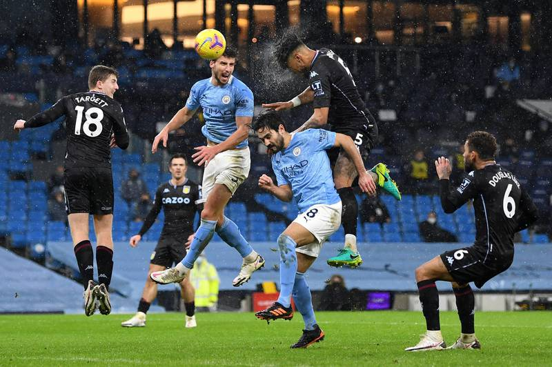 MANCHESTER, ENGLAND - JANUARY 20:  Tyrone Mings of Aston Villa jumps above Ilkay Gundogan of Manchester City to win a header during the Premier League match between Manchester City and Aston Villa at Etihad Stadium on January 20, 2021 in Manchester, England. Sporting stadiums around the UK remain under strict restrictions due to the Coronavirus Pandemic as Government social distancing laws prohibit fans inside venues resulting in games being played behind closed doors. (Photo by Shaun Botterill/Getty Images)