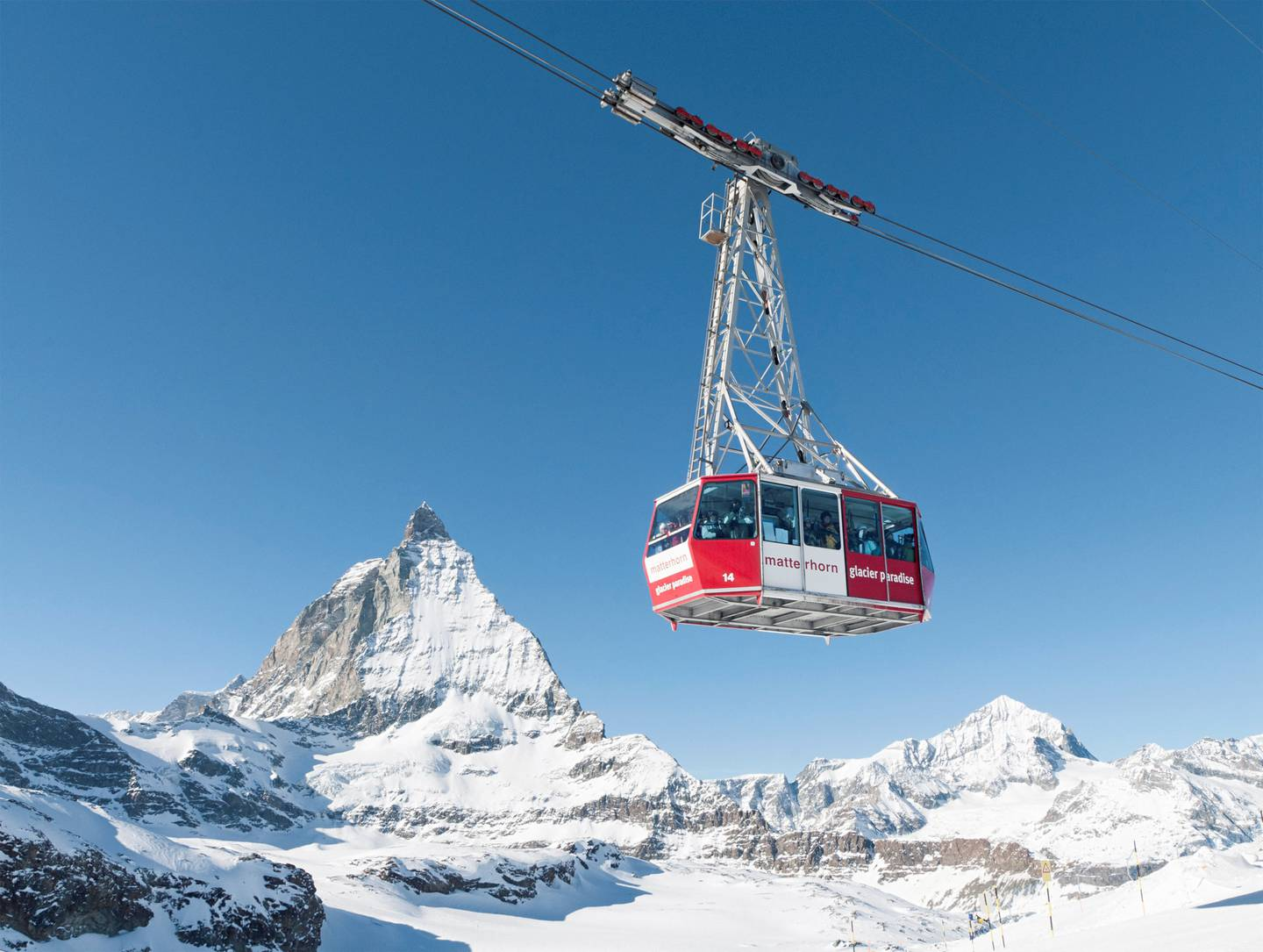 Zermatt, Switzerland - January 17, 2011: Skiers and snowboarders using the Matterhorn Glacier Paradise cable car, with the peak of the Matterhorn in the background.