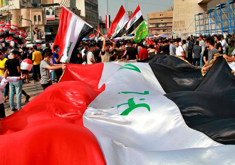 Protesters hold Iraqi flags in Tahrir Square during a demonstration calling for the government to resign, in Baghdad, Iraq, Sunday, Nov. 8, 2020. (AP Photo/Khalid Mohammed)