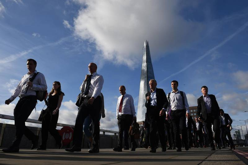 (FILES) In this file photo taken on June 05, 2017 Commuters walk across London Bridge, backdropped by The Shard, in London, after the bridge was partially re-opened following the June 3 terror attack. The number of workers on UK company payrolls slumped by a further 114,000 in July from June on fallout from the coronavirus pandemic, official data showed on August 11, 2020. A total 730,000 positions have been shed since March, when Britain went into lockdown over COVID-19, the Office for National Statistics said in a statement. / AFP / Justin TALLIS
