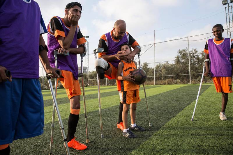 """Wahid Rabah, (center)the oldest member of Gaza's new amputee football team , with his son Abdullah,8, and other players during  the team's weekly practise session on July 16,2018. He lost his right leg during an Israeli military operation in 2006 called """"Summer Rain,"""" which was launched after an Israeli soldier was captured and taken into Gaza. (Photo by Heidi Levine for The National)."""
