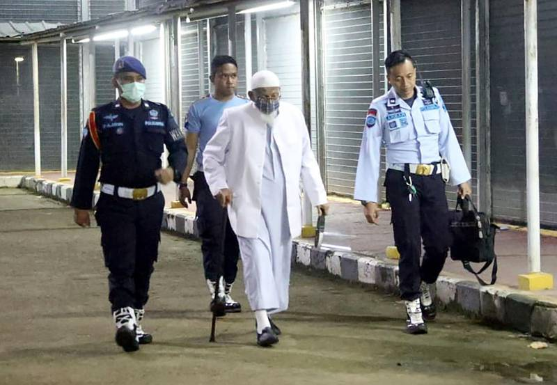 This handout photo taken on January 8, 2021 and released by Indonesia National Prison shows Abu Bakar Bashir, 82 (C), once synonymous with militant Islam in the world's biggest Muslim majority nation, being escorted by prison guards as he leaves the Gunung Sindur prison in Bogor, on the outskirts of Jakarta, after completing a 15 year prison term.  RESTRICTED TO EDITORIAL USE - MANDATORY CREDIT / AFP PHOTO / Indonesia National Prison / NO MARKETING - NO ADVERTISING CAMPAIGNS - DISTRIBUTED AS A SERVICE TO CLIENTS  / AFP / Indonesia National Prison / HANDOUT / RESTRICTED TO EDITORIAL USE - MANDATORY CREDIT / AFP PHOTO / Indonesia National Prison / NO MARKETING - NO ADVERTISING CAMPAIGNS - DISTRIBUTED AS A SERVICE TO CLIENTS