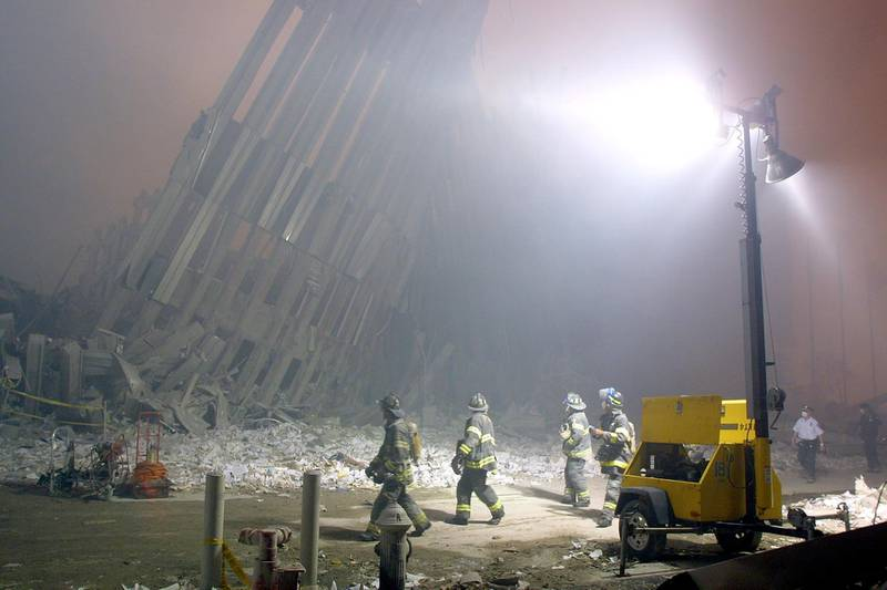 Firefighters make their way through the rubble of the World Trade Center 11 September 2001 in New York after two hijacked planes flew into the landmark skyscrapers. AFP PHOTO/Doug KANTER (Photo by DOUG KANTER / AFP)
