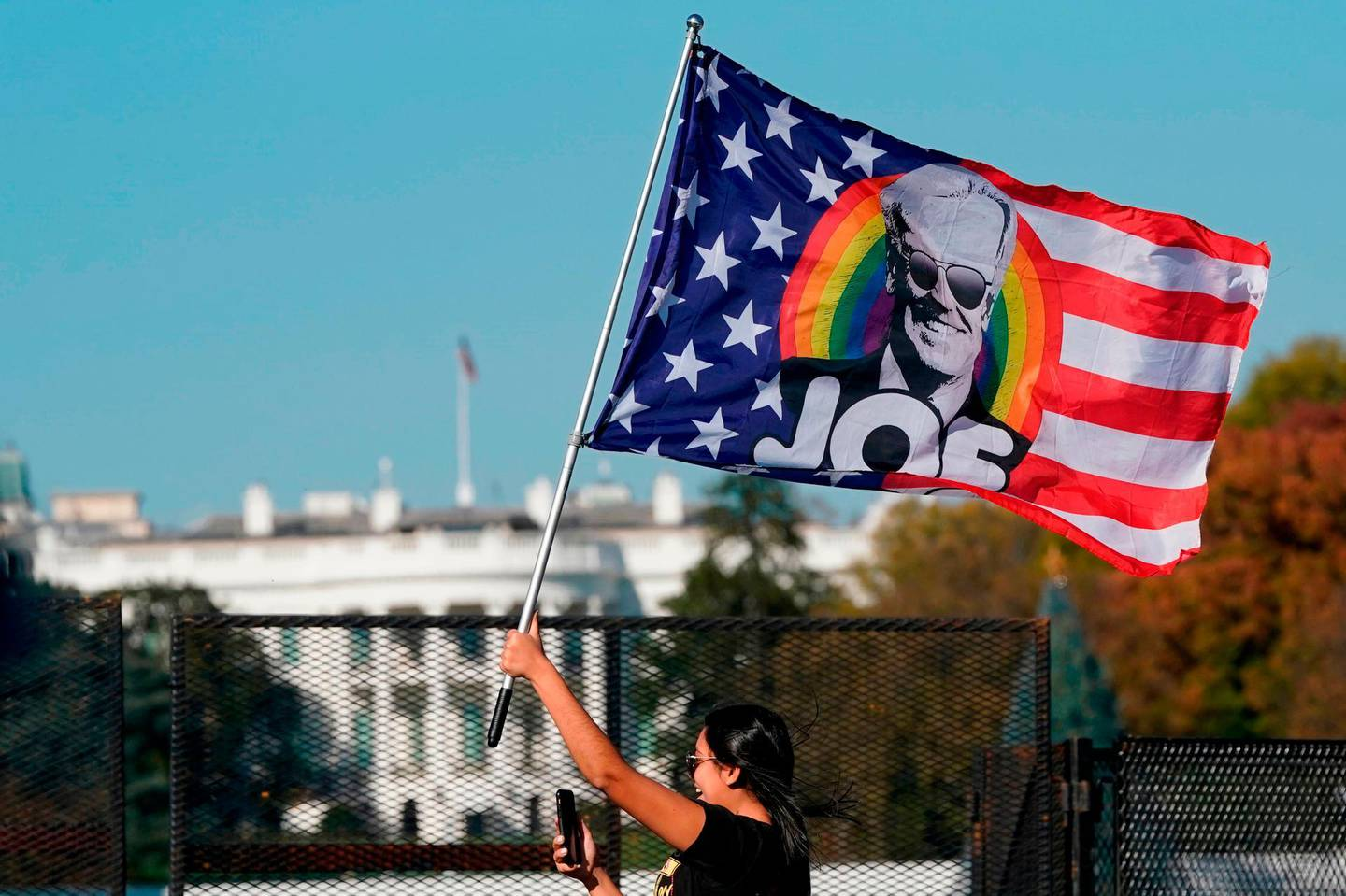 (FILES) In this file photo taken on November 07, 2020, a woman waves a Joe Biden flag as people celebrate on Black Lives Matter Plaza across from the White House in Washington, DC, after Biden was declared the winner of the 2020 presidential election.  Sentiment among Republican consumers plunged this month after US President Donald Trump lost his bid for a second term, according to a survey released on November 13, 2020. Fears rise that surging Covid-19 cases will worsen the economy also hit the University of Michigan's consumer sentiment index which fell to 77.0 early this month, a worse-than-expected drop of nearly six percent from October. / AFP / Alex Edelman