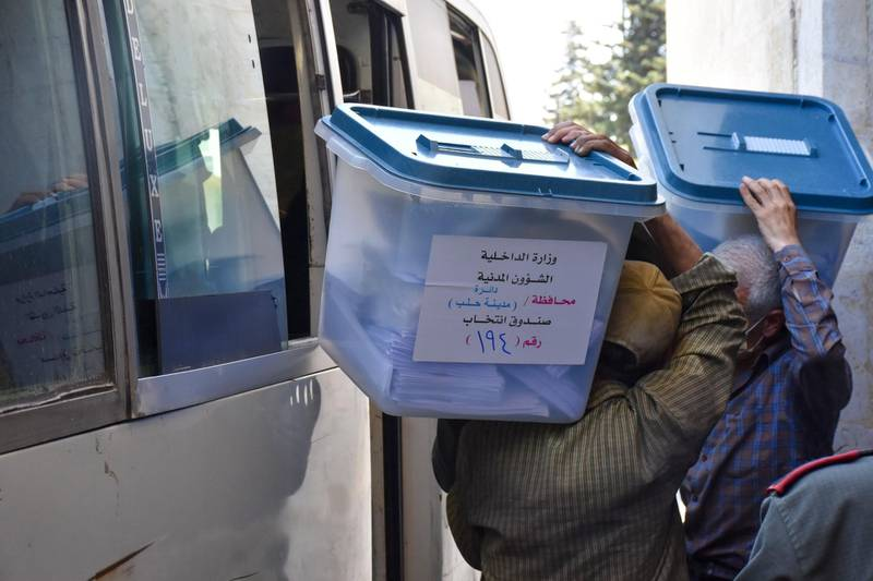 Syrian men carry ballot boxes onto a bus to hand them over to the police, who in turn will deliver them to polling stations on the eve of the parliamentary elections, in the Syrian city of Aleppo on July 18, 2020. More than 7,400 polling stations will open at 0430 GMT in government-held parts of Syria, including for the first time in former opposition strongholds. / AFP / -