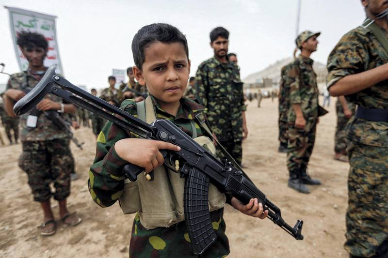 A Yemeni boy poses with a Kalashnikov assault rifle during a gathering of newly-recruited Huthi fighters in the capital Sanaa, to mobilize more fighters to battlefronts in the war against pro-government forces in several Yemeni cities, on July 16, 2017. (Photo by Mohammed HUWAIS / AFP)