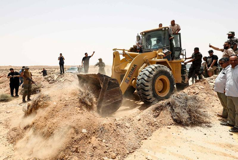 People cheer as an excavator removes rubble during a ceremony in the town of Buwairat al-Hassoun, on june 20, 2021, during a ceremony marking the reopening of 300-kilometre road between the cities of Misrata and Sirte.  Libya's unity government today reopened the coastal highway linking the country's east and west, that was cut off in 2019 as eastern-based military strongman Khalifa Haftar launched an offensive to seize the capital Tripoli.  It connects the war-torn North African country's border with Tunisia to its frontier with Egypt. / AFP / Mahmud TURKIA