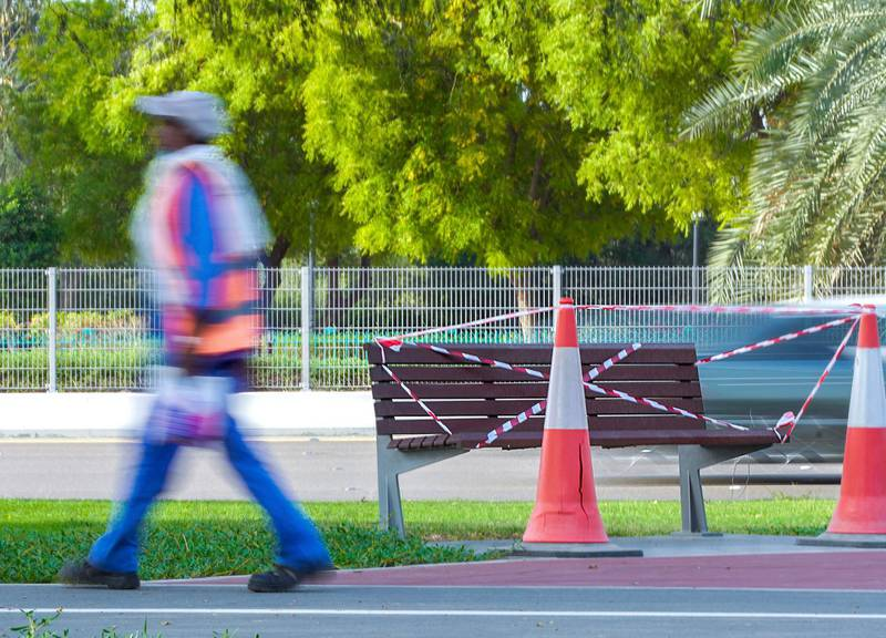 Abu Dhabi, United Arab Emirates, April 9, 2020.  A worker with his packed lunch walks by a cordoned off public bench, to curb the Coronavirus, along the Al Muhadhi pathway, Abu Dhabi.   Victor Besa / The NationalSection:  NAReporter: