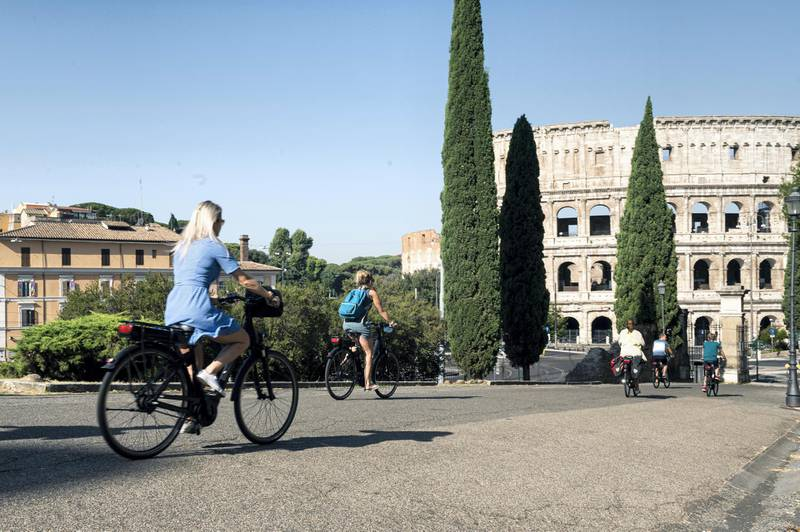 ROME, ITALY - JULY 31: Tourists on a bike tour cycle past the Colosseum on July 31, 2020 in Rome, Italy. The Italian government  is to offer a 70-per-cent subsidy, capped at 500 euros, for people who buy a new bicycle. Several European countries are exploring how their work force in post-COVID-19 commute can be environmentally sound, healthy and sustainable. Governments in Europe are fuelling the bicycle trend by offering buying incentives to customers. (Photo by Diana Bagnoli/Getty Images)