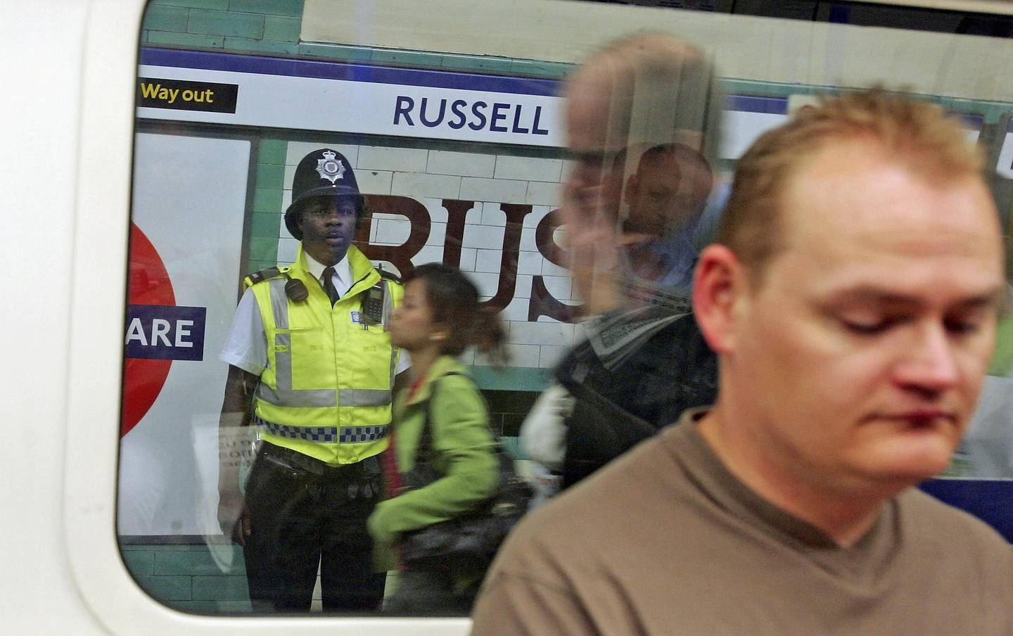 LONDON - JULY 07:  A British police officer watches commuters at Russell Square Underground Station on July 7, 2006 in London, England. On July 7, 2005 three Underground trains were hit by suicide bombers and a fourth blast on the number 30 double-decker bus at the junction of Tavistock Square and Upper Woburn place, killing 52 civilians.  (Photo by Scott Barbour/Getty Images)