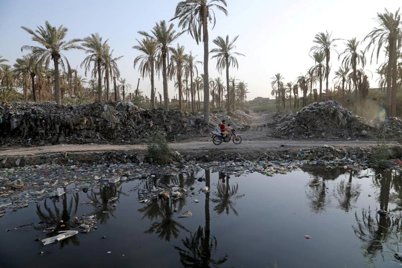 A motorcyclist rides along side the garbage floating on water canal running from the Euphrates River in Karbala, Iraq September 23, 2020. Picture taken September 23, 2020. REUTERS/Abdullah Dhiaa Al-Deen