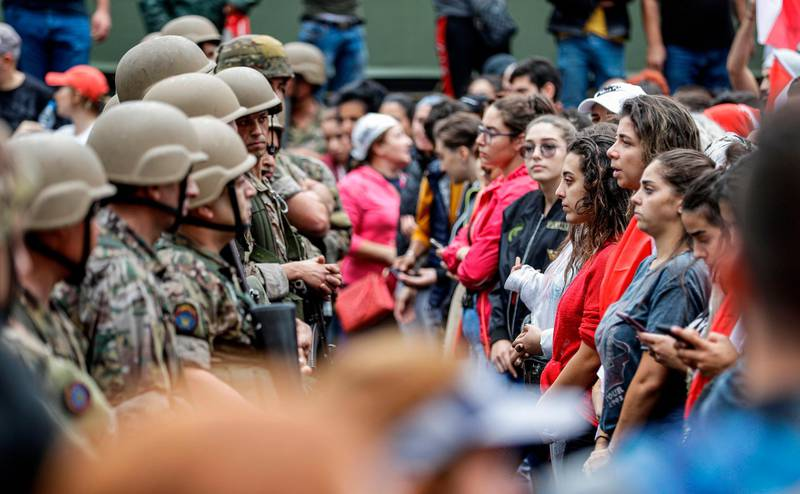 Female protesters stand in a line before Lebanese army soldiers during a demonstration on the seventh day of protest against tax increases and official corruption, in Zouk Mosbeh, north of the capital Beirut, on October 23, 2019. The almost one-week-old massive street protests in Lebanon, sparked by a tax on messaging services such as WhatsApp, have morphed into a united condemnation of a political system seen as corrupt and beyond repair. / AFP / JOSEPH EID