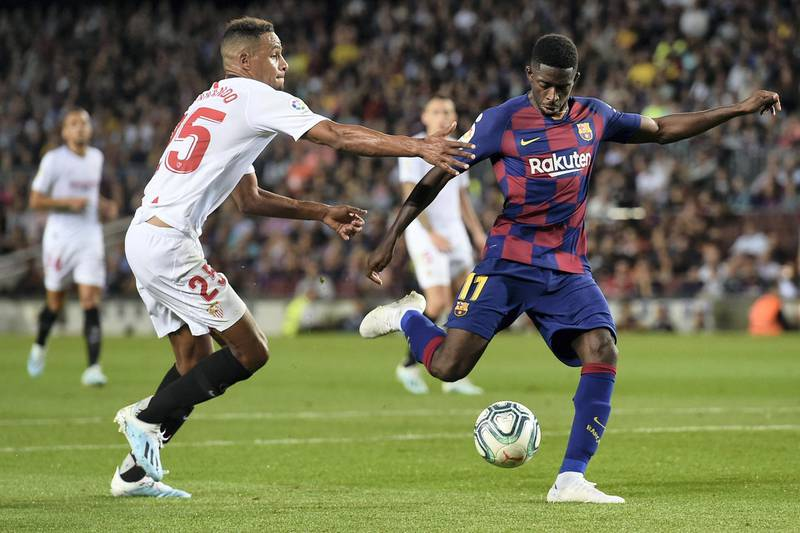 Sevilla's Brazilian midfielder Fernando (L) vies with Barcelona's French forward Ousmane Dembele during the Spanish league football match between FC Barcelona and Sevilla FC at the Camp Nou stadium in Barcelona on October 6, 2019. (Photo by Josep LAGO / AFP)