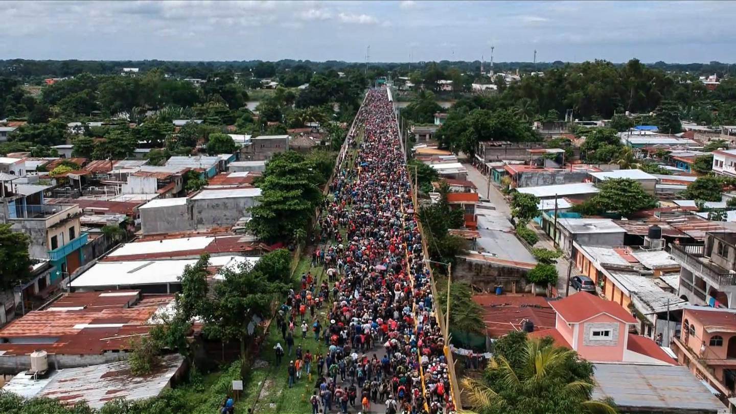 TOPSHOT - Aerial view of a Honduran migrant caravan heading to the US, as it reaches the Guatemala-Mexico international bridge in Tecun Uman, Guatemala on October 19, 2018. Honduran migrants who have made their way through Central America were gathering at Guatemala's northern border with Mexico on Friday, despite President Donald Trump's threat to deploy the military to stop them entering the United States. / AFP / Carlos ALONZO