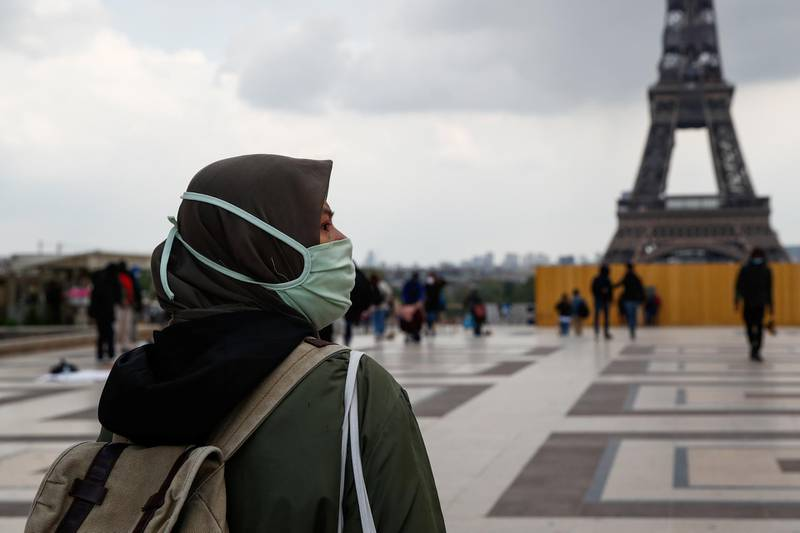 A woman, wearing a hijab and a protective face mask, walks at Trocadero square near the Eiffel Tower in Paris, France, May 2, 2021. Picture taken on May 2, 2021. REUTERS/Gonzalo Fuentes