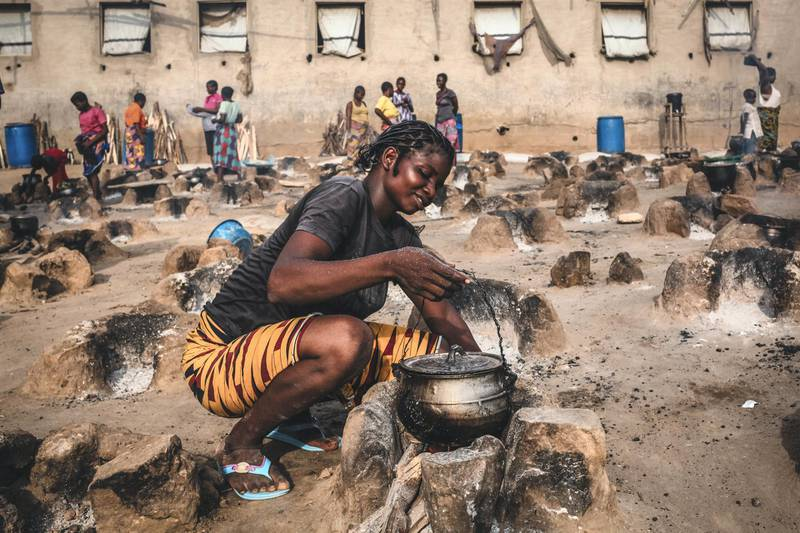 A young woman cooks an evening meal for her family in an open-air cooking area Abagana camp.