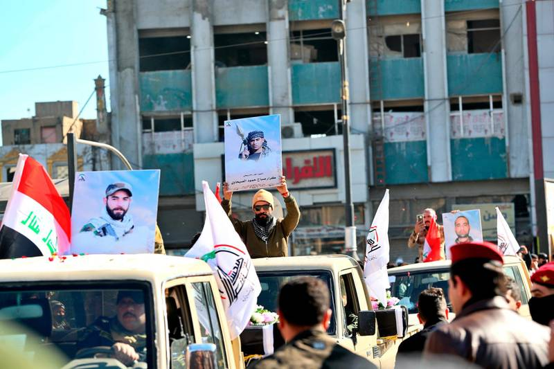 Popular Mobilisation Forces march with posters and symbolic coffins of their killed fighters in Tahrir Square, Baghdad, Iraq, Saturday, Dec. 26, 2020. (AP Photo/Khalid Mohammed)