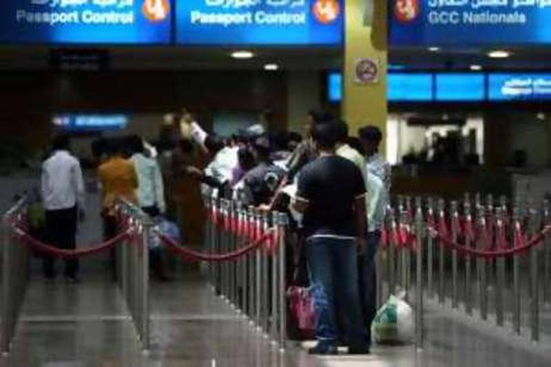 DUBAI, UNITED ARAB EMIRATES - JULY 7:  People wait in line at the passport control area in Terminal 1 arrivals section at the Dubai International airport in Dubai on July 7, 2009.  (Randi Sokoloff / The National)  For stock *** Local Caption ***  RS041-070709-DXB-STOCK.jpg