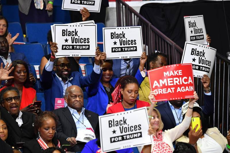 """Herman Cain (C,L) and supporters of US President Donald Trump """"Black Voices"""" listen to him speak during a campaign rally at the BOK Center on June 20, 2020 in Tulsa, Oklahoma. - Hundreds of supporters lined up early for Donald Trump's first political rally in months, saying the risk of contracting COVID-19 in a big, packed arena would not keep them from hearing the president's campaign message. (Photo by Nicholas Kamm / AFP)"""