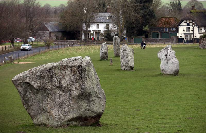 AVEBURY, UNITED KINGDOM - FEBRUARY 07:  Visitors walk besides the Neolithic stones at Avebury on February 7, 2013 in Wiltshire, England. A leading travel magazine has recently named the collection of stones - thought to have been constructed around 2600BC and the largest stone circle in Europe, as the second best heritage site in the world. The Wiltshire world heritage site has been placed ahead of much more recognisable sites including the Valley of the Kings in Egypt, Taj Mahal in India and the Forbidden City in China.  (Photo by Matt Cardy/Getty Images)