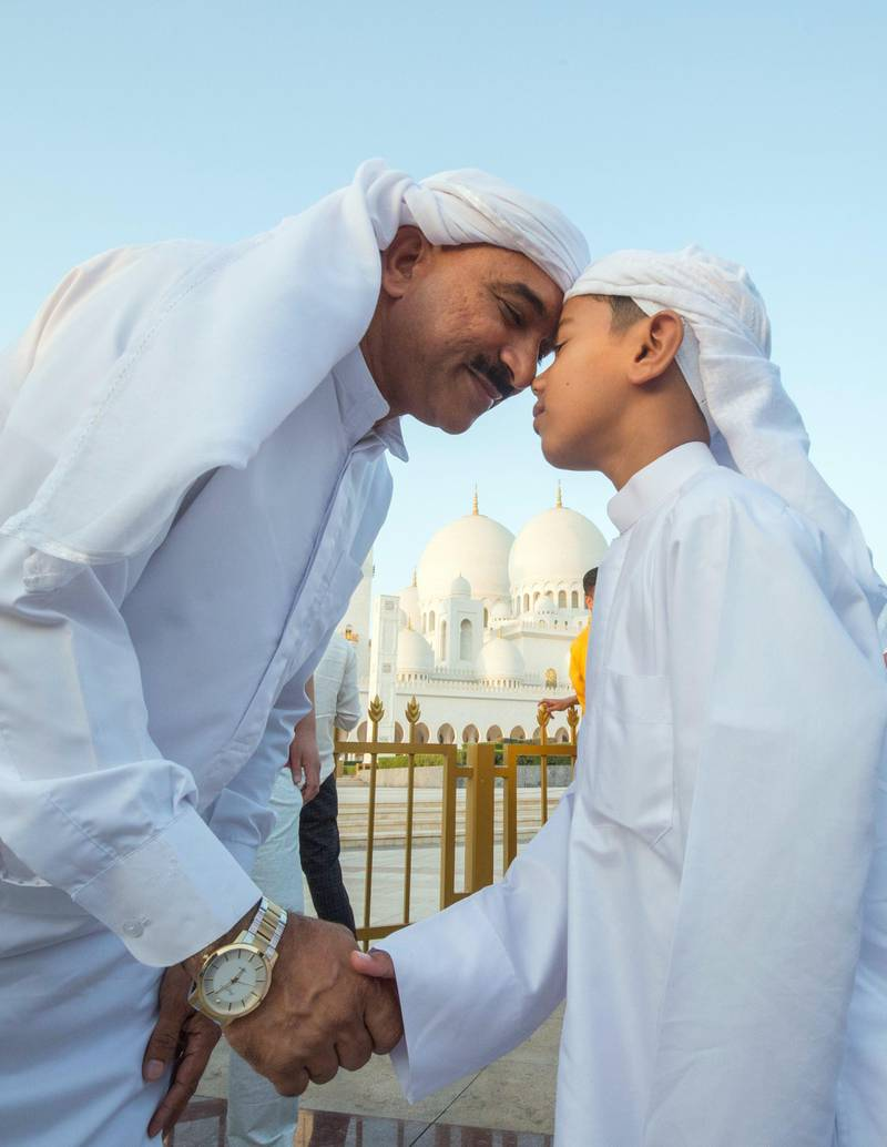 Abu Dhabi, UNITED ARAB EMIRATES - A father and his son greet each other after performing morning prayers on the first day of Eid-Al Fitr at the Sheikh Zayed Grand Mosque.  Leslie Pableo for The National