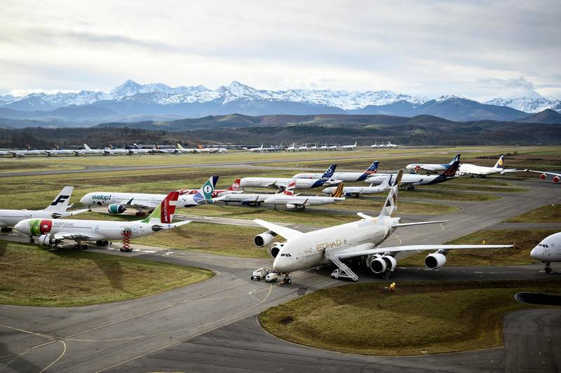 This picture taken on February 4, 2021, shows aeroplanes stocked by TARMAC Aerosave, an aircraft recycling and storage company, are pictured on the company parking area in Azereix, southwestern France. - At the foot of the snow-capped Pyrenees, dozens of planes from all over the world are carefully aligned like toys in a giant parking lot. Since the Covid-19 crisis, the Tarmac Aerosave company has been drowning in requests for storage from airlines. (Photo by Lionel BONAVENTURE / AFP) / RESTRICTED TO EDITORIAL USE, TO ILLUSTRATE THE EVENT AS SPECIFIED IN THE CAPTION