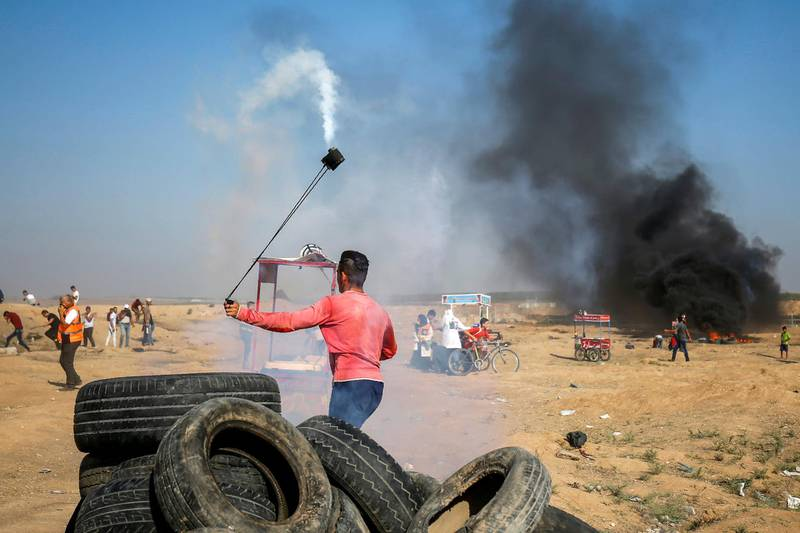 A Palestinian protester uses a slingshot to throw back a tear gas canister towards Israeli forces during clashes following a demonstration along the border east of Gaza City on July 6, 2018.  / AFP / SAID KHATIB
