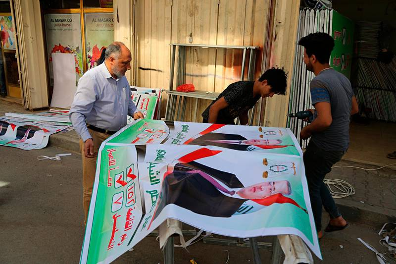 In this March 18, 2018 photo, Iraqis prepare an election banner in Baghdad, Iraq. Iran's influence is looming large as Iraqis prepare to head to the polls for parliamentary elections in May, with many concerned that Tehran may be looking to strengthen its political grip on Baghdad in the vote. (AP Photo/Karim Kadim)
