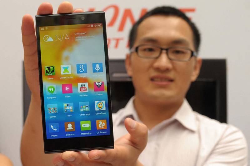 Hairui Sun, manager with Chinese smartphone maker Gionee poses with a Gionee Elife E7 handset during an event launch in Amritsar on April 19, 2014. The smartphone, which also has an 8-megapixel camera built in, uses the Amigo 2.0 operating system which is a derivative of the Android OS. AFP PHOTO/NARINDER NANU (Photo by NARINDER NANU / AFP)