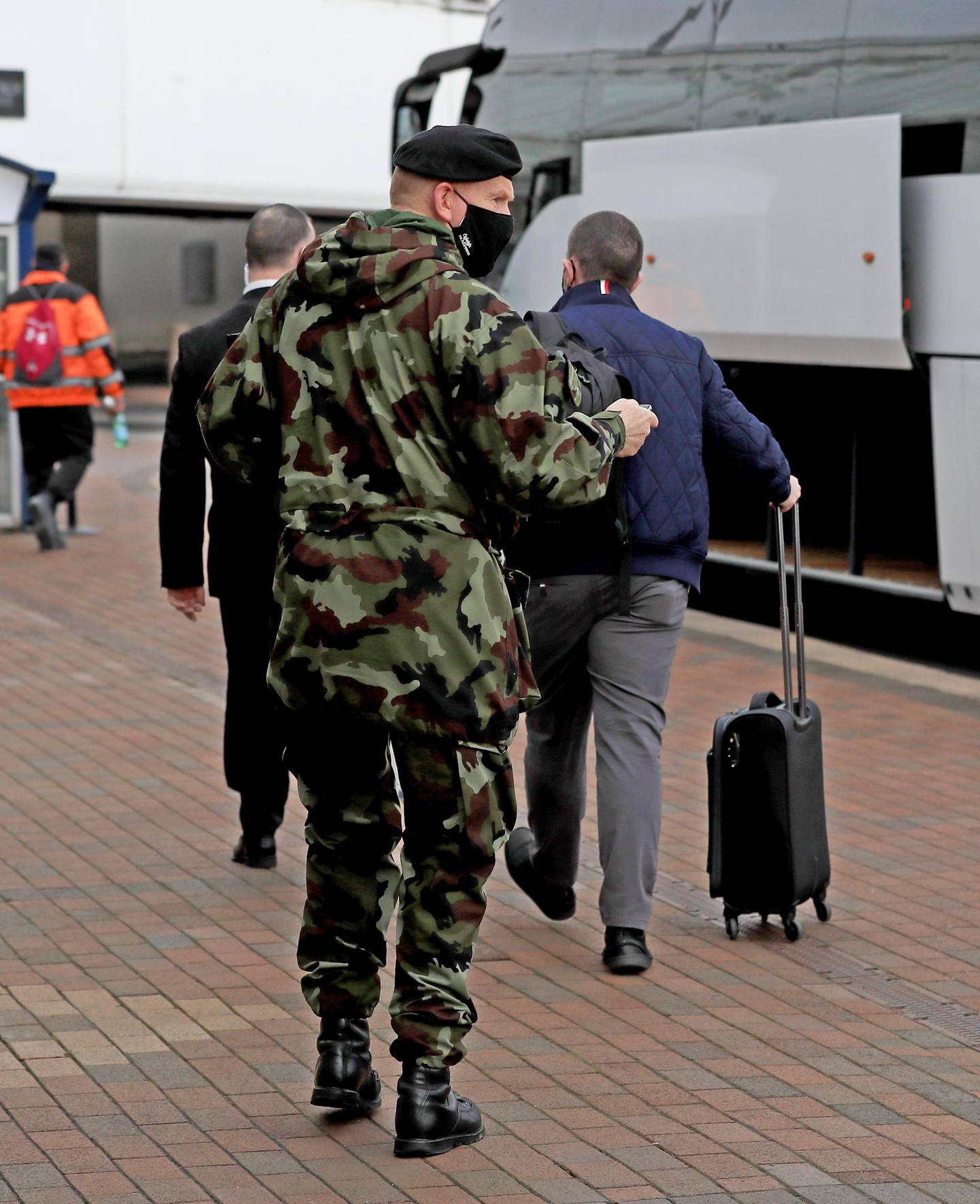 DUBLIN, IRELAND - MARCH 29: A passenger is escorted to a bus to be taken to the Crowne Plaza hotel for quarantine on March 29, 2021 in Dublin, Ireland. Last week, Ireland started requiring travelers from 33 high-risk countries to be shuttled to a mandatory 12-day hotel quarantine. Over the weekend, three quarantined travelers absconded from their hotel, forcing authorities to track them down. (Photo by Donall Farmer/Getty Images)